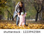 mother supporting baby daughter ...   Shutterstock . vector #1223942584