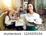 Stock photo portrait smiling young waitress standing in cafe the happy girl the waiter holds in bunches a tray 1224255154