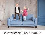 overjoyed boy and girl jump on...   Shutterstock . vector #1224390637