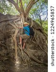a man climbing on tree roots...