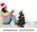 asian woman wearing santa hat... | Shutterstock . vector #1225115554