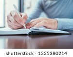 man hand writing in notepad.... | Shutterstock . vector #1225380214