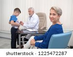 mother sitting in medical... | Shutterstock . vector #1225472287