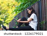 young asian woman writing on... | Shutterstock . vector #1226179021