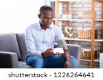 young man sitting on sofa... | Shutterstock . vector #1226264641