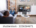 man lying on sofa watching... | Shutterstock . vector #1226264671