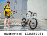 young man washing bicycle at... | Shutterstock . vector #1226551051