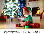 child opening present at... | Shutterstock . vector #1226786551