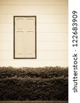 Vintage window on white cement wall - stock photo