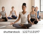 Stock photo yogi black woman and diverse group of young sporty people practicing yoga doing padmasana exercise 1227113197