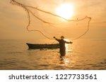 Fisherman Casting Net During...