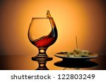 Glass of cognac with cheese plate - stock photo