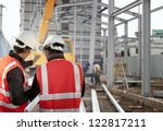 two foreman discussion on construction site - stock photo