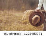 female hand holds hat on the... | Shutterstock . vector #1228483771