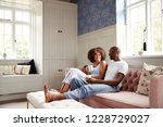 young black couple sitting... | Shutterstock . vector #1228729027