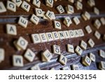 Scrabble game on wood forming the word serenity.
