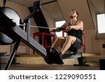 bearded fit man using rowing... | Shutterstock . vector #1229090551