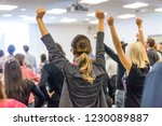 Small photo of Life coaching symposium. Speaker giving interactive motivational speech at business workshop. Rear view of unrecognizable participants feeling empowered and motivated, hands raised high in air.