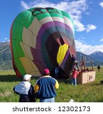 Couple watches a successful landing of a hot air balloon - stock photo