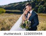 stylish groom hugs a beautiful...   Shutterstock . vector #1230555454