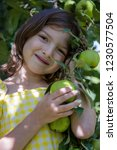 cute girl standing at the apple ...   Shutterstock . vector #1230577504