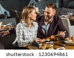 Small photo of Attractive smiling couple amorously looking at each other while having dinner in restaurant