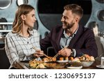 Small photo of Happy beautiful couple amorously looking at each other while having dinner in restaurant