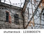 Small photo of Old ramshackle decrepit walls of soviet prison through barbed wire fence. Old Soviet prison Patarei, Russian fortress Defense Barracks and museum in Tallinn, Estonia