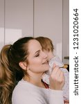 Small photo of Young mum trying to feed her uncooperative child. Lifestyle shot, at home, in the kitchen.