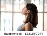 Small photo of Profile attractive young woman standing with closed eyes near window dreaming breathing fresh air thinking feels calmness and appeasement. Side view female wearing sportswear ready for yoga classes