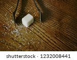 Small photo of Sugar tongs and sugar cube top view, shot with copy-space