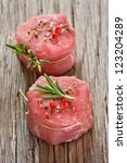 Fresh meat with spices and rosemary on a wooden background. - stock photo
