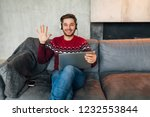 young smiling man sitting at...   Shutterstock . vector #1232553844