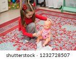 a little girl in red is played...   Shutterstock . vector #1232728507