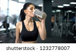 sporty woman drinking protein... | Shutterstock . vector #1232778007
