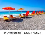 sunbeds with umbrellas at the... | Shutterstock . vector #1233476524