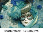 VENICE - 14 FEBRUARY: An unidentified woman dressed in typical Venetian mask decorated with green silk and gold detailing  perform at the most famous European Carnival on February 14, 2010 in Venice. - stock photo