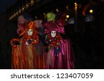 VENICE - 14 FEBRUARY: An unidentified  two women masked in silk costumes glowing in the dark street perform at the most famous European Carnival on February 14, 2010 in Venice. - stock photo