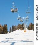 Charilift at ski resort transporting skiers to the summit. - stock photo