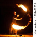 Small photo of Grodno, Belarus - April, 30, 2012 fire show, dancing with flame, male master fakir juggler with fire works on street arts festival, fire trick
