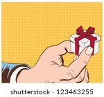 gift box in hand with red bow... | Shutterstock .eps vector #123463255