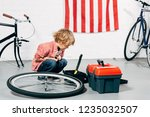 child sitting near tools boxes... | Shutterstock . vector #1235032507