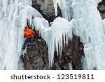 Ice climber on his way up on a frozen waterfall in South Tyrol, Italy. - stock photo