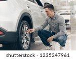 male customer examining wheels... | Shutterstock . vector #1235247961