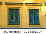 two green windows on a yellow... | Shutterstock . vector #1235252707