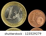 Two used coin - one euro and euro cent - isolated on black background. Closeup view. - stock photo