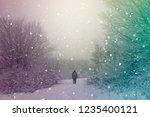 man walking on snowy path in... | Shutterstock . vector #1235400121