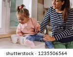 mother and daughter in kitchen. ... | Shutterstock . vector #1235506564