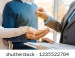 realtor woman giving house keys ... | Shutterstock . vector #1235522704