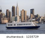 A New York City ferry boat crosses the Hudson with a view of the skyline. - stock photo